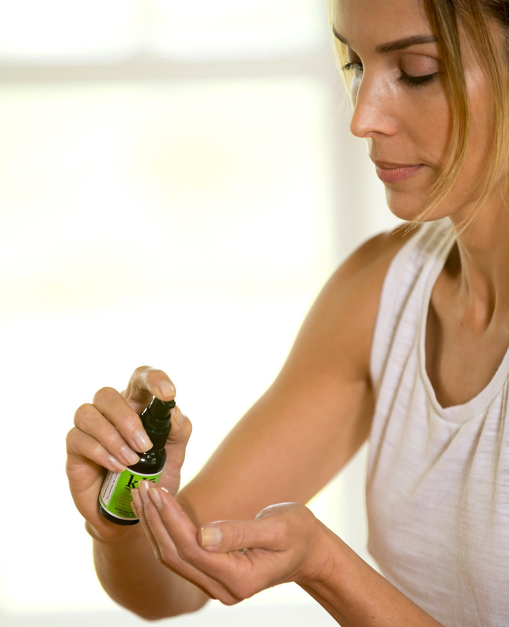 Tan model pumping Klō Organic Beauty serum into her hands.