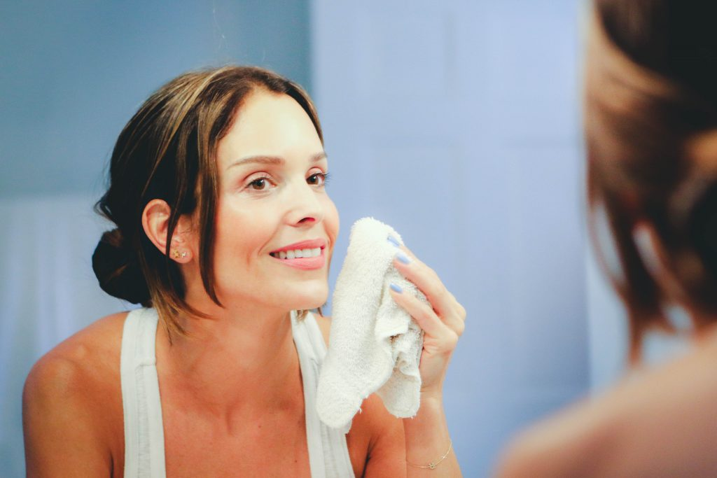 Woman with mature skin using wash cloth to remove oil cleanser